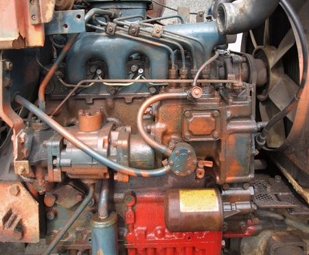 repaired: The aging motor of an old tractor is being repaired Editorial