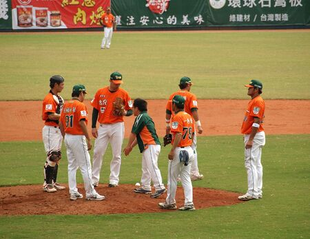 PINGTUNG, TAIWAN, APRIL 8: Players and coach talk with pitcher Wordekemper of the President Lions in Pro Baseball game against the Lamigo Monkeys. The Lions won 2:0 on April 8, 2012 in Pingtung.