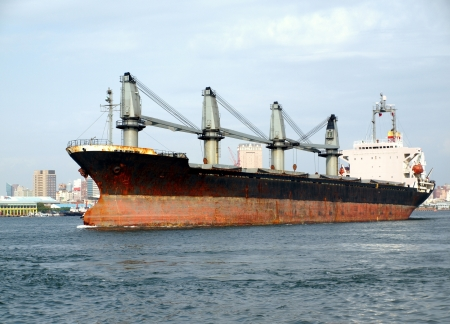 A large cargo ship moves towards the exit of Kaohsiung harbor Stock Photo - 13816513