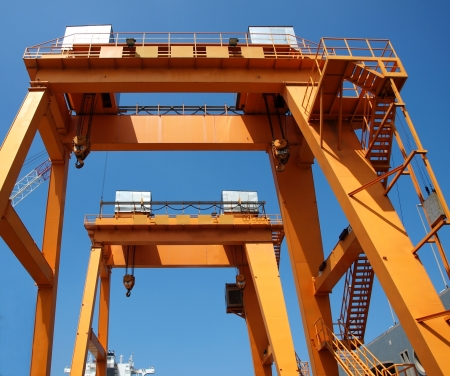 Two yellow overhead gantry cranes against a blue sky photo