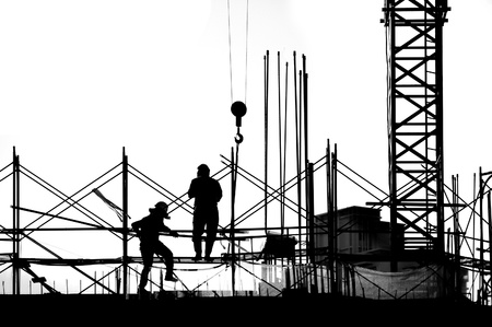 Construction workers and crane seen in outline photo