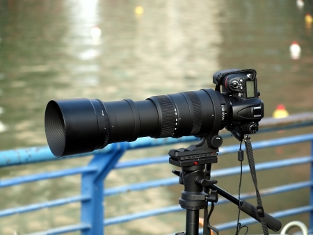 attachement: A single lens reflex camera on a tripod with a long telephoto lens attached