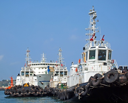 tug boat: Three tugboats in port with a large ship in the background