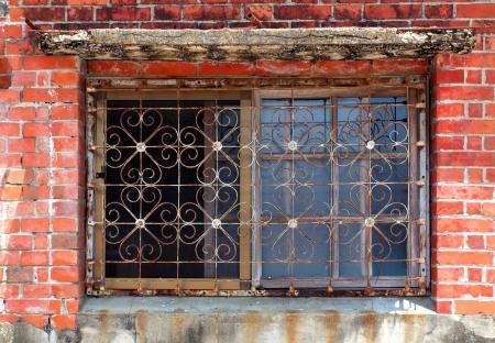 Una casa de ladrillo con una ventana que tiene flores en forma de barras Foto de archivo