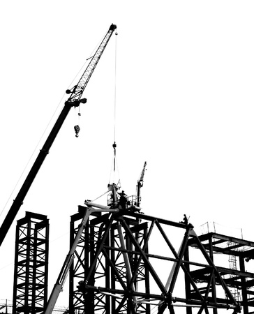Steel construction with crane and workers in silhouette