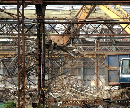 corrosion: Remnants of an old factory that are torn down by a demolition machine