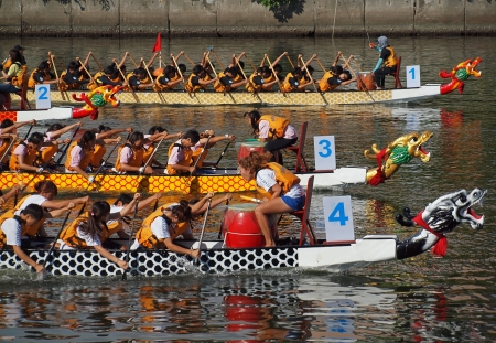 unison: KAOHSIUNG, TAIWAN - JUNE 11: Four unidentified teams compete in the 2013 Dragon Boat Races on the Love River on June 11, 2013 in Kaohsiung Editorial