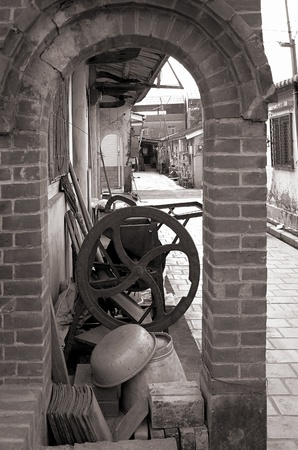 farm equipment: Lane in an old Chinese village with vintage farm equipment