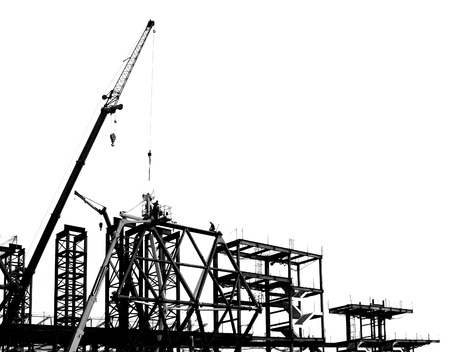 Construction site with crane and scaffolding seen as a silhouette   Stock Photo