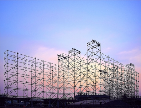 Complex scaffolding setup for a stage for an outdoor concert seen at sunset