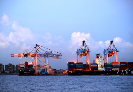 compared: KAOHSIUNG, TAIWAN -- SEPTEMBER 12: Container terminal at Kaohsiung Port at evening time. The port authority announced plans to increase container volume by 3% in 2013 compared to the previous year, on September 12, 2013 in Kaohsiung.   Editorial