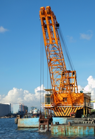 silt: A large yellow dredging crane scoops silt from the harbor