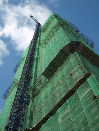 construction safety: The massive frame of a modern building construction site with a crane attached on the building exterior