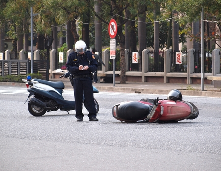 involving: Kaohsiung, Taiwan - 8 Febbraio 2014 Un poliziotto registra i dettagli di un incidente stradale che comportano un motorino