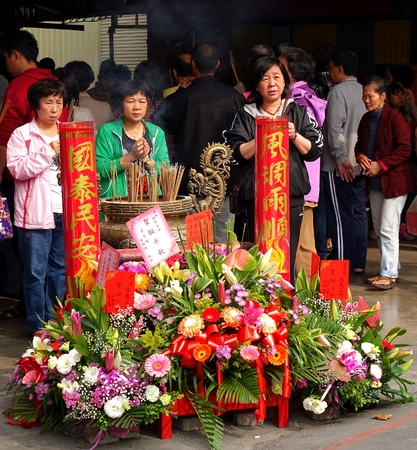 KAOHSIUNG, TAIWAN -- MARCH 2, 2014: Unidentified worshipers burn incense and say prayers at a ceremony at the Fu De Temple in Kaohsiung City.