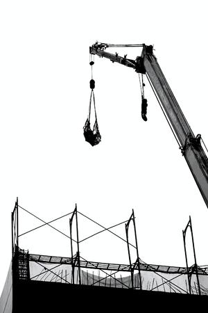 A crane lowers a load onto a construction site   photo
