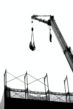 lowers: A crane lowers a load onto a construction site