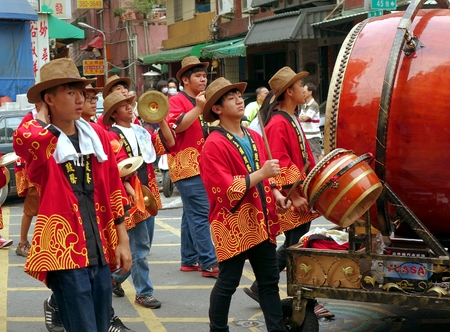 chinese drum: KAOHSIUNG, TAIWAN -- APRIL 20, 2014: Young men in indentical hats and robes play percussion instruments in a religious procession.