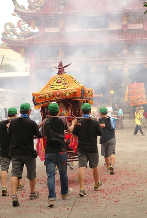 palanquin: KAOHSIUNG, TAIWAN -- APRIL 20, 2014: Young men carry a sedan chair in which is seated a deity through the smoke of firecrackers towards a temple.