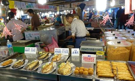 fish vendor: KAOHSIUNG, TAIWAN -- MARCH 20, 2014: A vendor sells fried fish, fish sausages and fish balls at a traditional Chinese outdoor market.