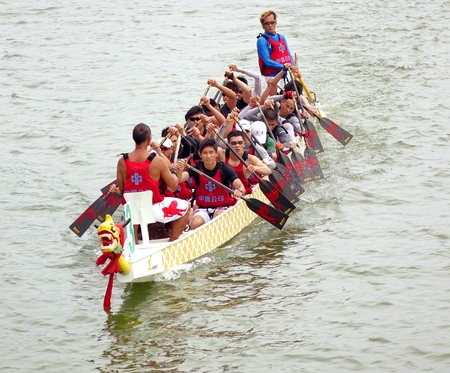 competes: KAOHSIUNG, TAIWAN - MAY 25, 2014: A team from China Steel Corporation competes in the 2014 Dragon Boat Races on the Lotus Lake.