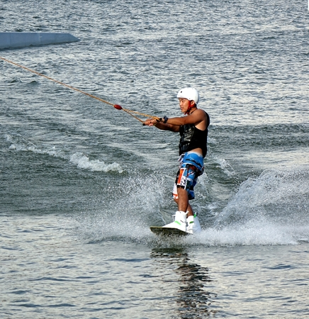 wakeboarding: KAOHSIUNG, TAIWAN -- MAY 25, 2014: An unidentified male enjoys wakeboarding on the Lotus Lake in Kaohsiung.