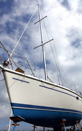 A sailing yacht is placed on a scaffold for repair and maintenance photo