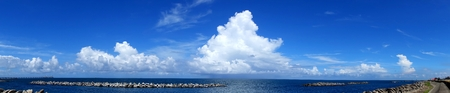 breakwaters: Beautiful panorama of ocean and sky and clouds with concrete breakwaters
