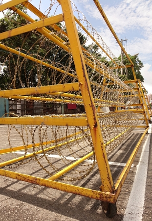 deter: A yellow painted metal barrier with razor wire is used to guard a military installation Editorial