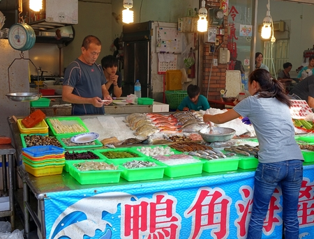 KAOHSIUNG, TAIWAN -- OCTOBER 11, 2014: A customer chooses fresh fish to have it prepared by a seafood restaurant on the island of Cijin.