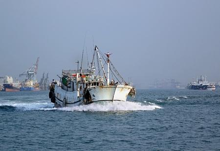 pescando: Kaohsiung, Taiw�n - 11 de octubre 2014: Un barco de pesca tradicional china surcando aguas del puerto de Kaohsiung.