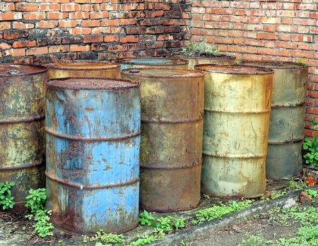 corroding: Corroding oil drums in a deserted building pollute the ground Stock Photo