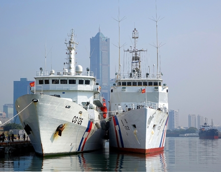 coastguard: KAOHSIUNG, TAIWAN -- JANUARY 1, 2015: Two large coastguard vessels are anchored in Kaohsiung Port. In the background is 85 story Tuntex Tower.