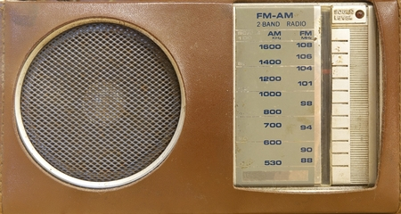 An old portable transistor radio in a brown plastic cover