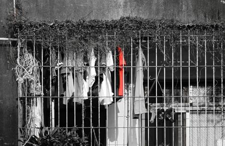 rejas de hierro: En un balcón cubierto vallado con barras de hierro cuelga ropa a secar