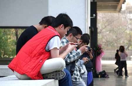 seemingly: KAOHSIUNG, TAIWAN -- FEBRUARY 19, 2015: Young people are deeply absorbed with their mobile devices, seemingly oblivious to their surroundings.