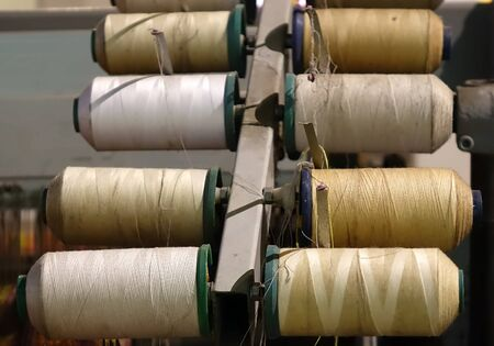 old spools: An old piece of textile manufacturing equipment with various spools of yarn Stock Photo