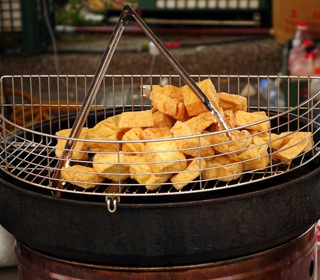 stinky: An outdoor vendor offers deep fried chunks of stinky fermented tofu, a popular Chinese snack.
