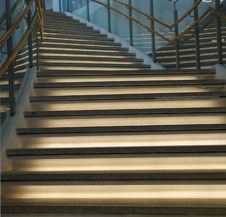indirect: A curved staircase leading upwards with indirect lighting