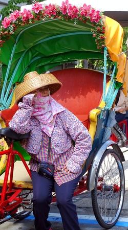 rikscha: Kaohsiung, Taiwan - 25. Juli 2015: Eine weibliche Zyklus Rikschafahrer, trägt einen traditionellen Hakka-Stil Strohhut, wartet auf neue Kunden.