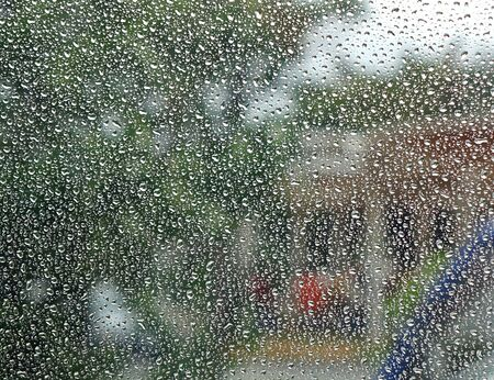 precipitation: Raindrops form a dense pattern on a window pane