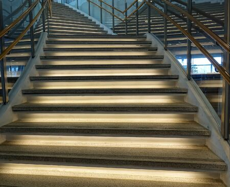 banisters: A curved staircase with illuminated stairs and banisters
