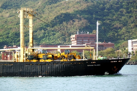 freighter: KAOHSIUNG, TAIWAN -- AUGUST 12, 2015: The Panamanian freighter Grand Tajima enters Kaohsiung Port with a cargo of construction equipment and excavators. Editorial