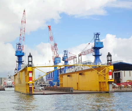 drydock: KAOHSIUNG, TAIWAN -- AUGUST 12, 2015: A floating dry dock is surrounded by construction cranes in the wharf area of Kaohsiung Port.