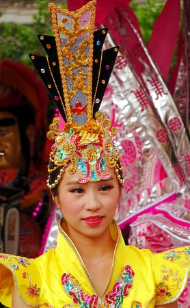 headgear: KAOHSIUNG, TAIWAN -- AUGUST 15, 2015: A beautiful female dancer with an elaborate headgear and yellow costume awaits her turn at the outdoor Third Prince temple carnival.