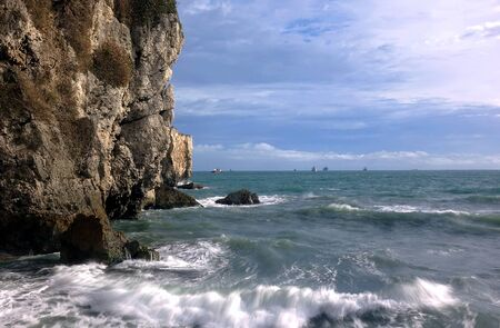 rocks water: Beautiful ocean scene with steep cliff descending into the sea, on the horizon are several large ships. Stock Photo