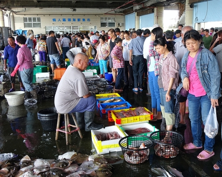 check out: KAOHSIUNG, TAIWAN -- SEPTEMBER 6, 2015: Shoppers at the Sinda Port fish market check out the fish and seafood that is on sale in baskets and crates. Editorial