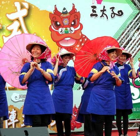 KAOHSIUNG, TAIWAN -- AUGUST 15, 2015: Women dressed in traditional Chinese Hakka costumes perform a dance with bamboo umbrellas at the Third Prince temple carnival.