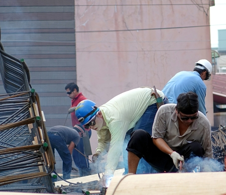building foundation: KAOHSIUNG, TAIWAN -- SEPTEMBER 20, 2015: Construction workers with welding equipment assemble a metal structure used to reinforce the building foundation.