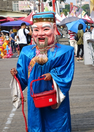 KAOHSIUNG, TAIWAN -- OCTOBER 17, 2015: A man dressed up as the traditional Chinese God of Wealth begs for lucky charm donations.